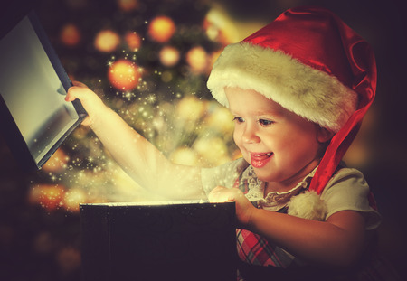 baby open present: Christmas miracle, magic gift box and a child baby girl Stock Photo