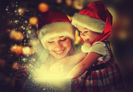 adornos navidad: Navidad caja de regalo m�gico y una ni�a mujer feliz madre de familia y su hija Foto de archivo