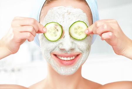 limpieza: Chica joven divertida con una m�scara para la cara la piel y los pepinos en los ojos Foto de archivo