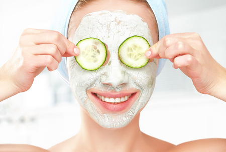 cucumber: Funny young girl with a mask for skin face and cucumbers on eyes