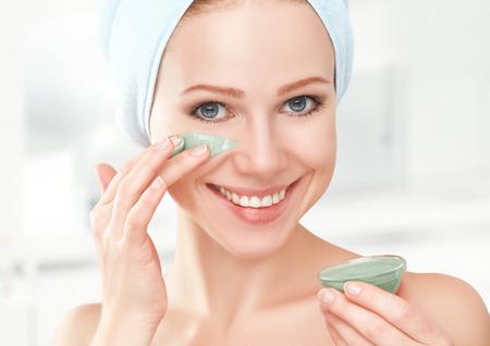 얼굴 피부 관리를위한 욕실과 마스크에서 아름 다운 소녀