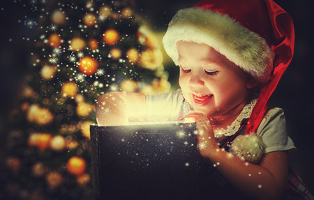 Christmas miracle, magic gift box and a child baby girl Archivio Fotografico