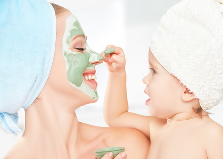 salon spa: family beauty treatment in the bathroom. mother and daughter baby girl make a mask for a face skin