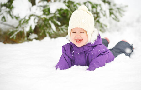 Happy child baby girl in snow outdoors in winter photo