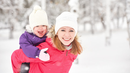 family with two children: happy family mother and baby girl daughter playing and laughing in winter outdoors in the snow