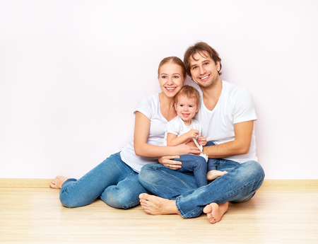 Happy family on the floor near the empty blank  wall in the apartment bought on mortgage