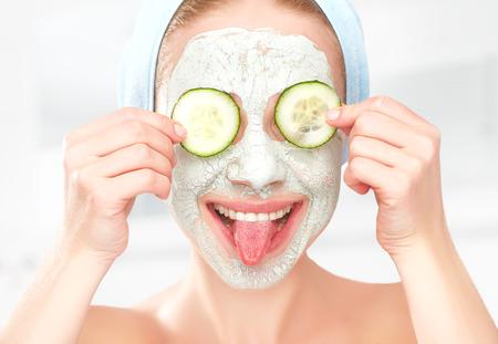 masaje facial: Chica joven divertida con una m�scara para la cara la piel y los pepinos en los ojos Foto de archivo