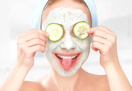 body mask: Funny young girl with a mask for skin face and cucumbers on eyes