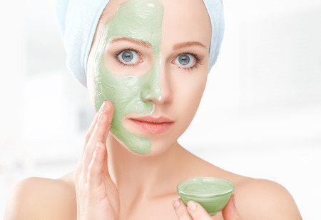 woman face cream: beautiful girl in the bathroom and mask for facial skin care
