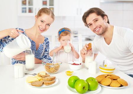 Happy family mother, father, child baby daughter having breakfast at home
