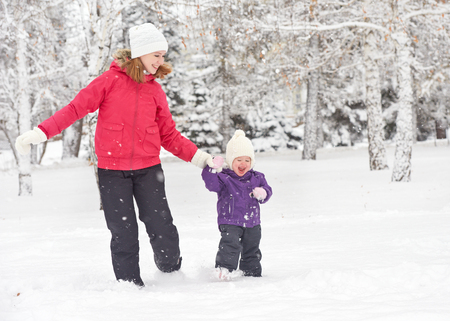 happy family mother and baby girl daughterтrun, walk playing  in winter outdoors in the snow photo