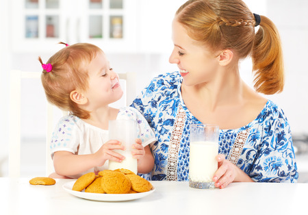 milk and cookies: happy family mother and baby daughter  child girl at breakfast: biscuits with milk