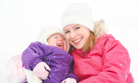 happy family mother and baby girl daughter playing and laughing in winter outdoors in the snow photo