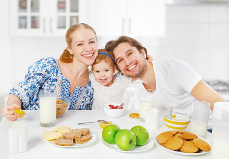 human milk: Happy family mother, father, child baby daughter having breakfast at home