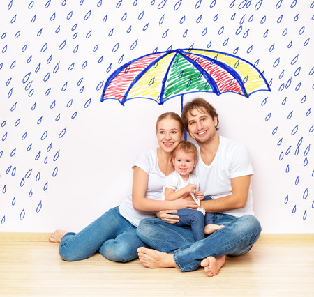 concept: the social protection of the family. family took refuge from the miseries and rain under an umbrella Фото со стока