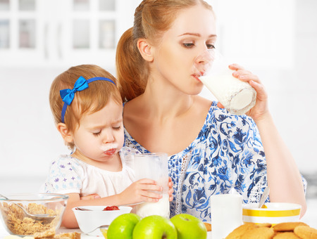 human milk: happy family mother and baby daughter  child girl at breakfast: biscuits with milk