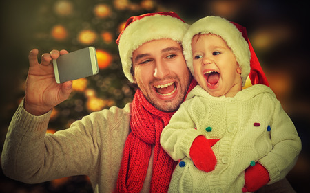 selfie  in Christmas. happy family father dad playing with baby daughter and photographed on a mobile phone photo