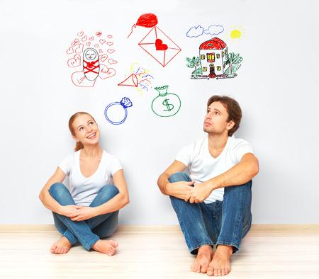 概念。新しい家、子供の財政の福利を夢見て若い幸せな家族のカップル
