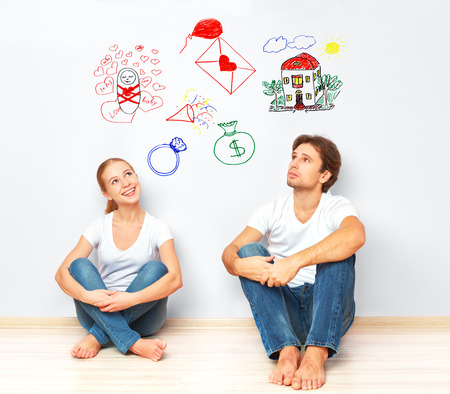 estate planning: concept. young happy family couple dreaming of new house, child, financial well-being Stock Photo