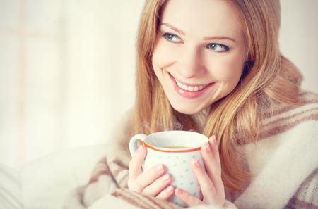 幸せな若い女性は冬の朝自宅で毛布とコーヒーのカップの下で日光浴します。 写真素材 - 35162710