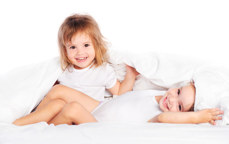 twin sister: happy little girls twins sister in bed under the blanket having fun, smiling