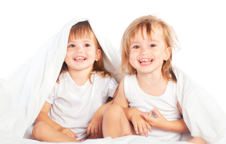 twins: happy little girls twins sister in bed under the blanket having fun, smiling
