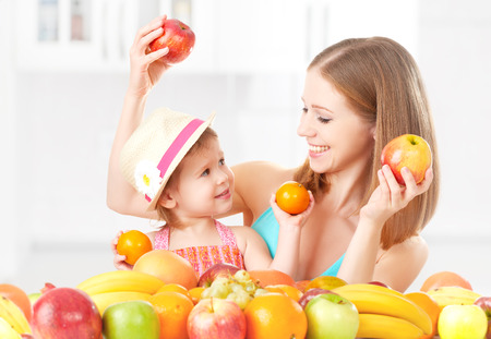 happy family mother and daughter little girl, eat healthy vegetarian food, lots of fruit