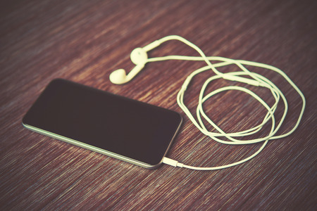 electronic music: smart phone mobile phone and headphones on the table Stock Photo