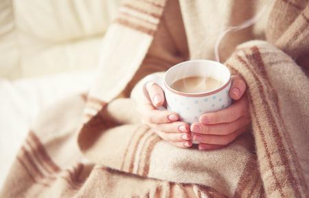 resfriado: taza caliente del calentamiento caf� caliente en las manos de una ni�a Foto de archivo