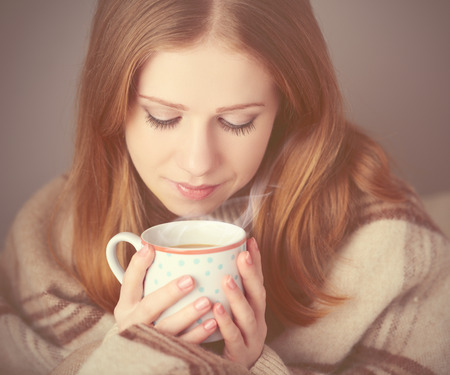 cold woman: happy girl  is basking  under a blanket and a cup of coffee on a winter morning at home Stock Photo