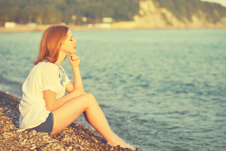 sad girl sitting on the coast on beach and looks into the distance at sea