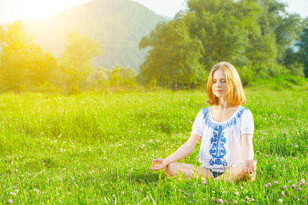 yoga meditation: young woman doing yoga, sitting in lotus position on green grass