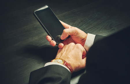 phone in the hands of a businessman in dark colors photo