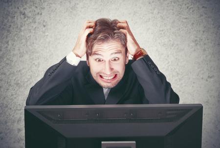 fails: young man at the computer fails, stress, depression