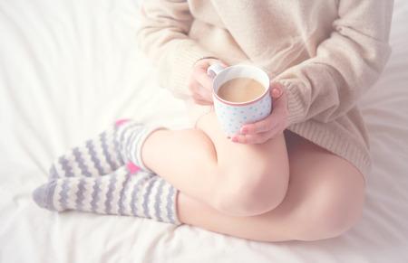 jambes de fille chaussettes de laine chauds et une tasse de café, de réchauffement matin d'hiver à la maison dans son lit