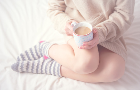 breakfast in bed: legs of girl warm woolen socks and a cup of coffee warming, winter morning at home in bed