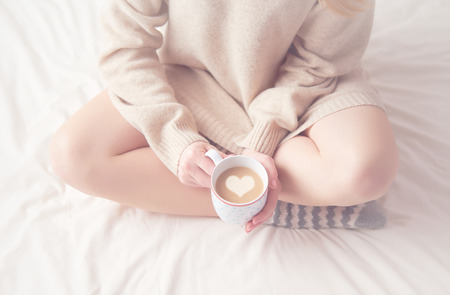 bed: legs of girl warm woolen socks and a cup of coffee warming, winter morning at home in bed