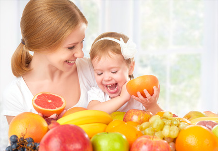 woman eating fruit: happy family mother and daughter little girl, eat healthy vegetarian food, lots of fruit