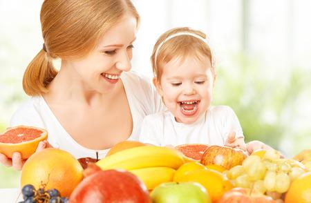 gelukkig gezin moeder en dochter klein meisje, eet gezond vegetarisch eten, veel fruit Stockfoto