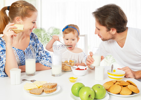familia comiendo: Feliz madre de familia, padre, hija bebé niño que desayunan en casa