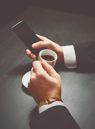 computer devices: phone and a cup of coffee in the hands of a businessman. stylish business still life in dark colors