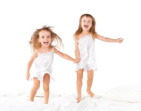 happy family at home. kids twin sisters jumping on the bed, playing and laughing Foto de archivo