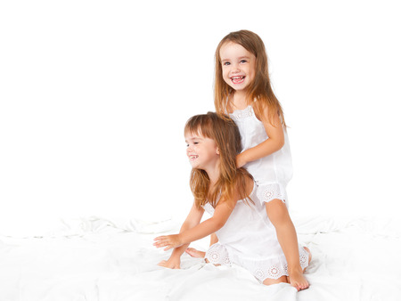 leaping: happy family at home. kids twin sisters jumping on the bed, playing and laughing Stock Photo