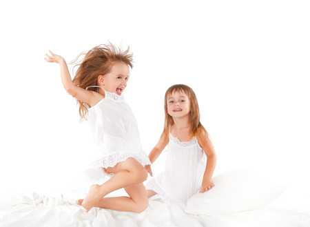 twin: happy family at home. kids twin sisters jumping on the bed, playing and laughing Stock Photo