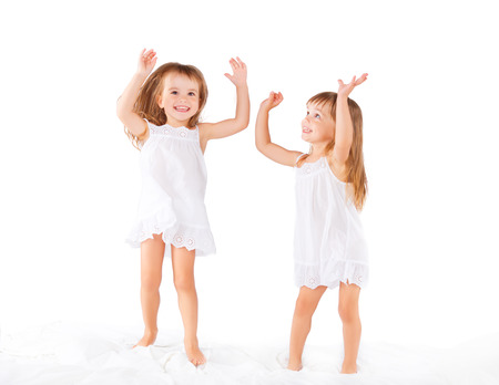 child in bed: happy family at home. kids twin sisters jumping on the bed, playing and laughing Stock Photo