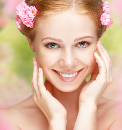 clear skin: Beauty face of the young happy beautiful woman with pink flowers in her hair Stock Photo