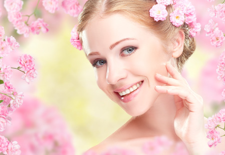 Beauty face of the young happy beautiful woman with pink flowers in her hair Stock Photo