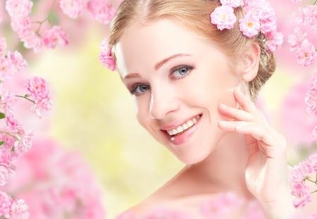 Cara de la belleza de la joven y bella mujer feliz con flores de color rosa en el pelo Foto de archivo - 36801217