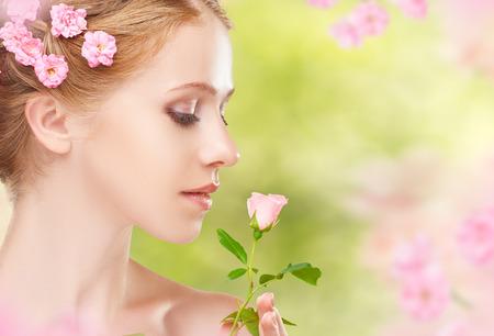 olfato: Cara de la belleza de la joven y bella mujer con flores de color rosa en el pelo
