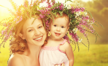 laughing: happy laughing family, daughter hugging mother in wreaths of summer flowers in nature Stock Photo